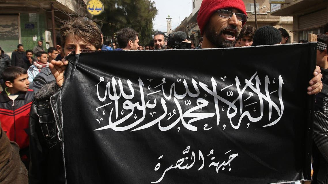 In this Friday, March 1, 2013 file photo, anti-Syrian President Bashar Assad protesters hold the Jabhat al-Nusra flag, as they shout slogans during a demonstration, in Kafranbel, Idlib province, northern Syria. Under the relative calm of Syria's shaky cease-fire, peaceful protests in opposition-held parts of the country have re-emerged, but in addition to Syrian President Bashar Assad's government, protesters have found another authority to topple: Al-Qaeda's affiliate in Syria, the oppressive Nusra Front group. (AP Photo/Hussein Malla, File)