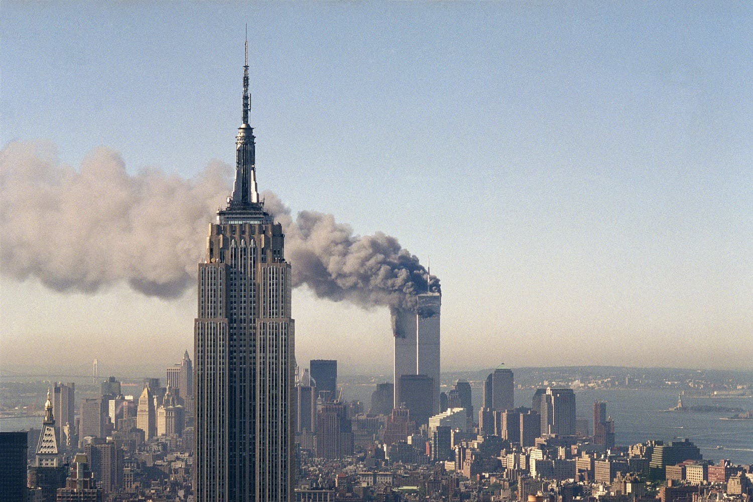 The twin towers of the World Trade Center burn behind the Empire State Building in New York after terrorists crashed two planes into the towers causing both to collapse (File Photo: AP)