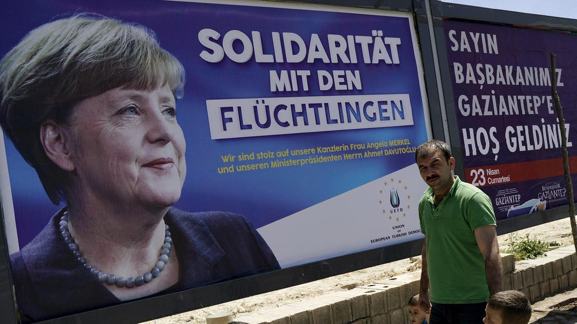 "People walk past a banner with picture of German Chancellor Angela Merkel on a main street in Gaziantep, Turkey, April 23, 2016. The banner in German reads, ""Solidarity with refugees. We are proud of our Chancellor Angela Merkel and Prime Minister Ahmet Davutoglu"". REUTERS"