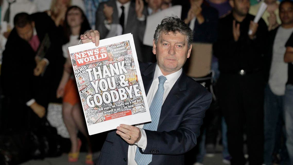 News of the World tabloid newspaper Editor, Colin Myler poses with a front page of the last edition as he leads his staff out of the headquarters of News International, the publisher of News of the World newspaper, in London, Saturday, July 9, 2011. News of the World is to cease publication following the edition this Sunday July 10. News of the World is closing down following criticism and public outrage over allegations that some of the paper's journalists paid police for information and hacked into the voicemail of the mobile phones of young murder victims and the grieving families of dead soldiers, and other public figures. (AP Photo/Sang Tan)
