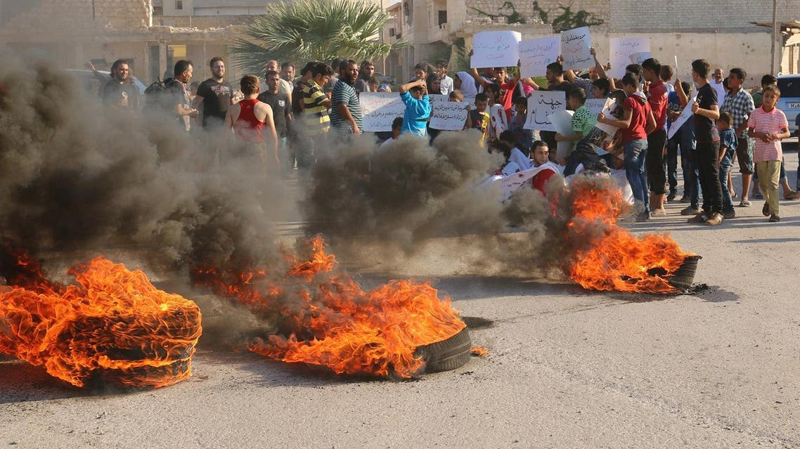 People gather near burning tyres during a demonstration against forces loyal to Syria's president Bashar al-Assad and calling for aid to reach Aleppo near Castello road in Aleppo. (Reuters)