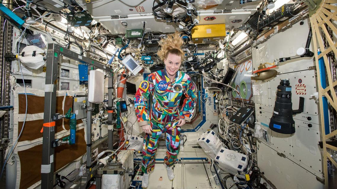 NASA  astronaut Kate Rubins aboard the International Space Station wearing a hand-painted spacesuit decorated by childhood cancer patients at the University of Texas MD Anderson Cancer Center in Houston. NASA said Rubins will chat from the space station with patients during a 20-minute call on Friday, Sept. 16, 2016. (NASA via AP)