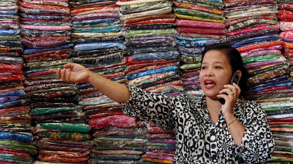 Fadhilah Arshad, a businesswoman, talks to a supplier as she sells cloth at her bazaar in Kuala Lumpur December 1, 2009. (Reuters)