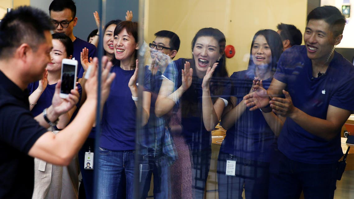 Staff members applaud a customer as he arrives to purchase Apple's new iPhone 7 at an Apple store in Beijing, China, September 16, 2016. (Reuters)