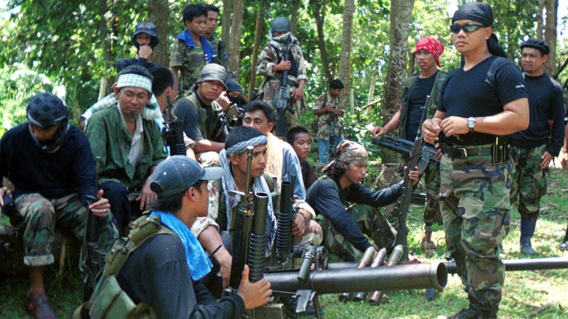 Undated file photo of Abu Sayyaf spokesman Abu Sabaya (right foreground), with militants in Basilan, the Philippines. Abu Sayyaf, a group in the southern Philippines that professes radical ideology but which is better known for banditry and kidnappings, has declared allegiance to ISIS.