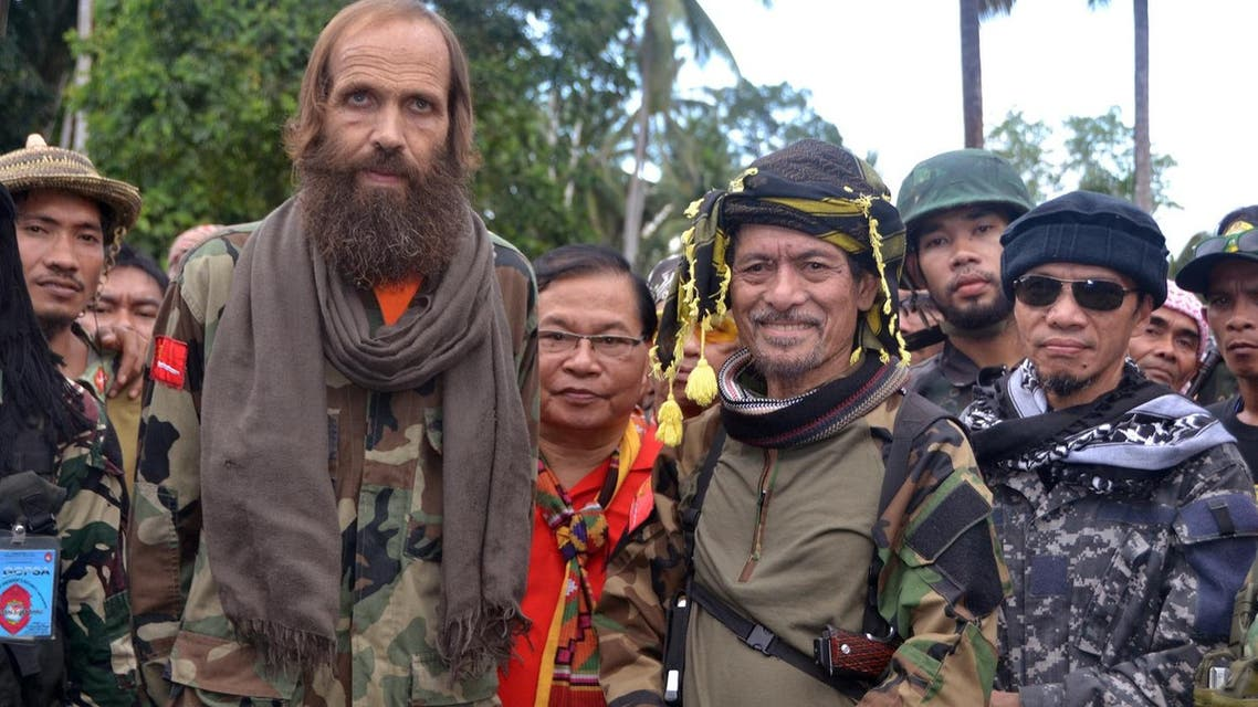 Released Norwegian hostage Kjartan Sekkingstad, front row left, poses with Moro National Liberation Front Chairman Nur Misuari, front row second right, after being turned over by ransom-seeking Abu Sayyaf extremists in Indanan township on Jolo island in southern Philippines Sunday, Sept. 18, 2016. Sekkingstad, who was kidnapped last year along with two Canadians and a Filipino, was released Saturday and was turned over Sunday to Misuari, who in turn turned him over to Presidential adviser Jesus Dureza. (AP Photo/Nickee Butlangan)