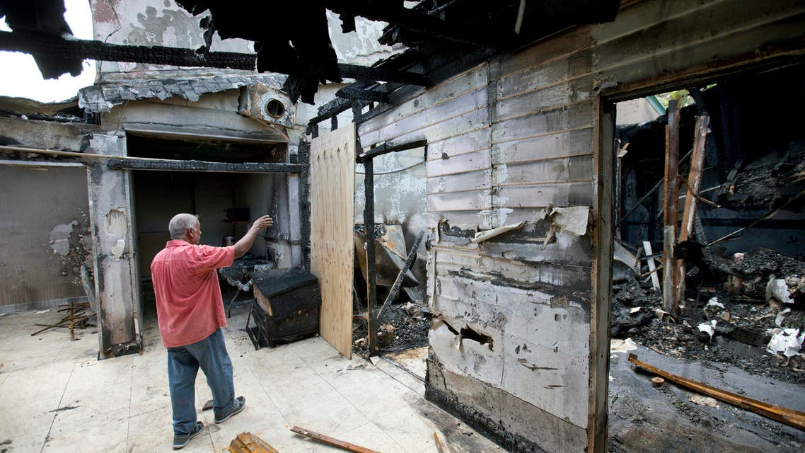 Farhad Khan, who has attended the Islamic Center of Fort Pierce for more than seven years, shows members of the media its charred remains, Thursday, Sept. 15, 2016, in Fort Pierce, Fla. AP