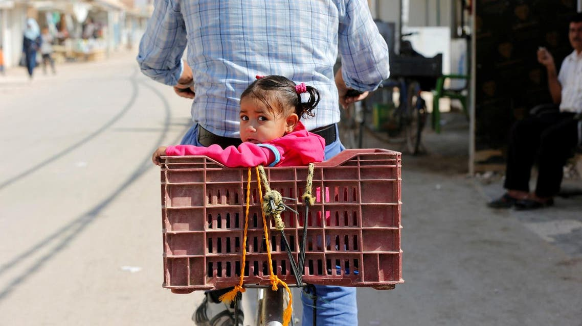 A Syrian refugee rides a bicycle with his daughter in the Al-Zaatri refugee camp in the Jordanian city of Mafraq. (Reuters)