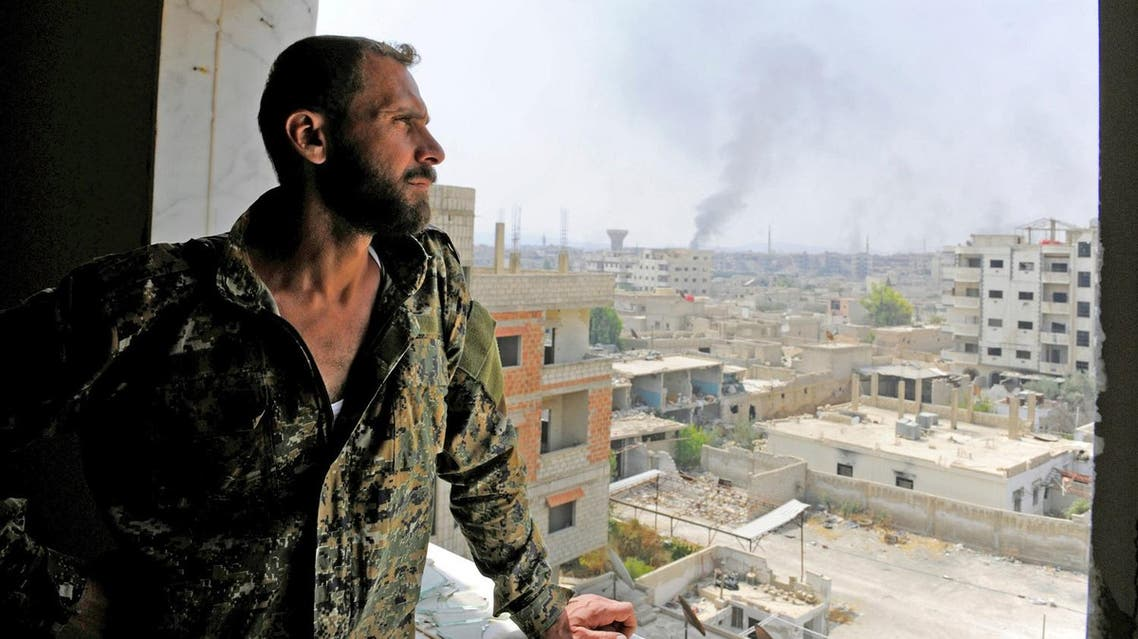A Syrian army soldier looks out from a window as smoke rises from the besieged Damascus suburb of Daraya. (File photo: Reuters)