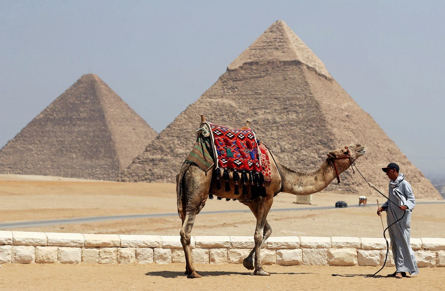A man waits for tourists to rent his camel in front of the Great Giza pyramids on the outskirts of Cairo, Egypt, August 31, 2016. (Reuters)
