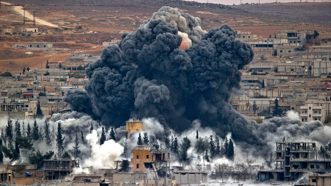 FILE -- In this Nov. 17, 2014 file photo, smoke rises from the Syrian city of Kobani, following an airstrike by the US led coalition, seen from a hilltop outside Suruc, on the Turkey-Syria border. After months of losing ground in Iraq and Syria, the Islamic State group is showing signs of the wear and tear, with commanders on the ground saying they are seeing an increase in desertions. But the jihadis appear to be lashing back with more terrorist and chemical attacks. (AP Photo/Vadim Ghirda, File)