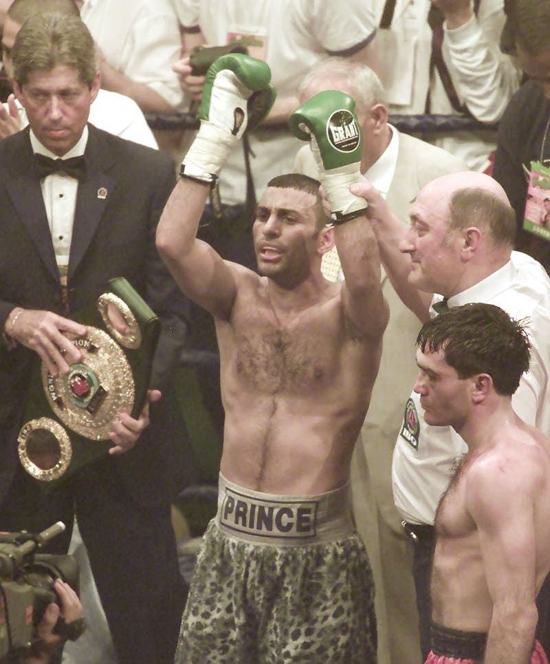 Prince Naseem Hamed of Britain, center, with arms raised get the points decision against Manuel Calvo from Spain for the IBO Featherweight Championship of the World at the London Arena in London in 2002. (AP)