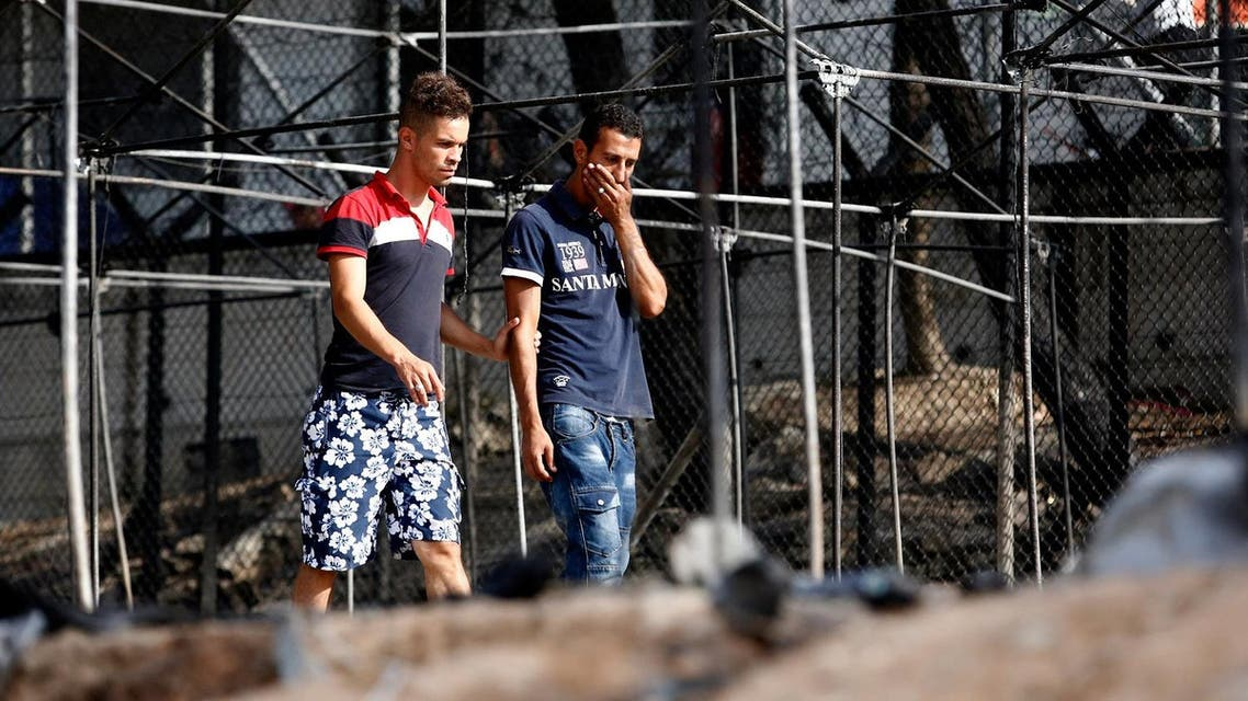 A migrant (R) reacts as he walks next to the remains of burned tents at the Moria migrant camp, after a fire that ripped through tents and destroyed containers during violence among residents. (Reuters)