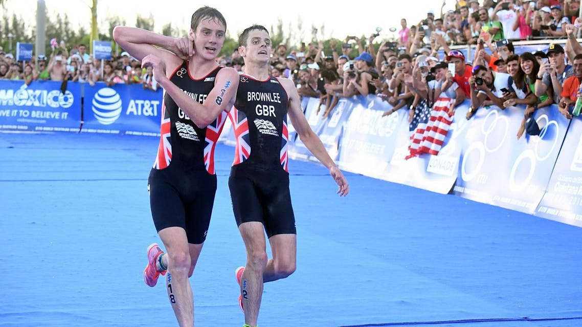 Britain's Alistair Brownlee, left, helps his brother Jonny to get to the finish line during the Triathlon World Series event in Cozumel, Mexico, Sunday Sept. 18, 2016. (AP)
