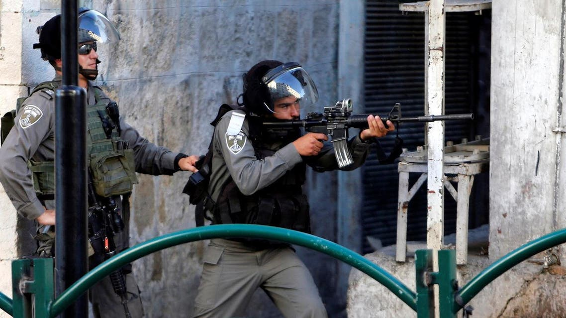 Israeli border policeman aims his weapon towards Palestinian protesters during clashes in the West Bank city of Hebron. (Reuters)