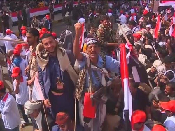 يمني يتحدى الحوثيين وينزل شعارهم بميدان السبعين بصنعاء