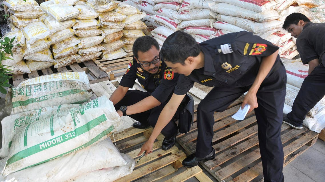 Customs officers examine bags of fertilizer, some of the 30 tonnes seized from a ship from Malaysia, at a customs office in Denpasar, Bali, Indonesia on September 22, 2016. AP