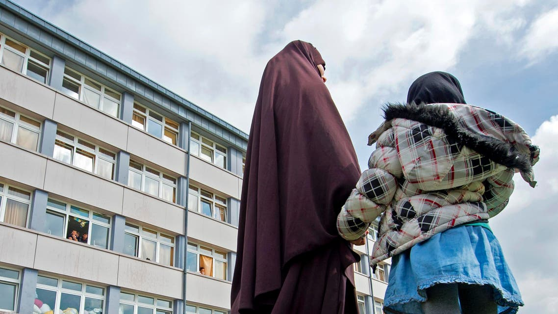 In this April 17, 2015 picture a Chechen woman and her child stand in front of the reception center for refugees in Schneeberg, eastern Germany. (AP)
