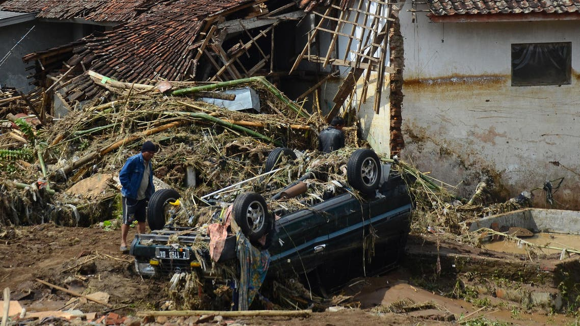 A man inspects a damaged vehicle in a village badly hit by a flash flood in Garut, West Java, Indonesia, Wednesday, Sept. 21, 2016. (AP)