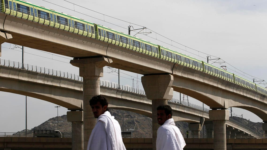A Mecca Metro train passes over Muslim pilgrims' heads towards Mina ahead of the hajj main ritual at Mount Arafat outside Mecca, Saudi Arabia. AP