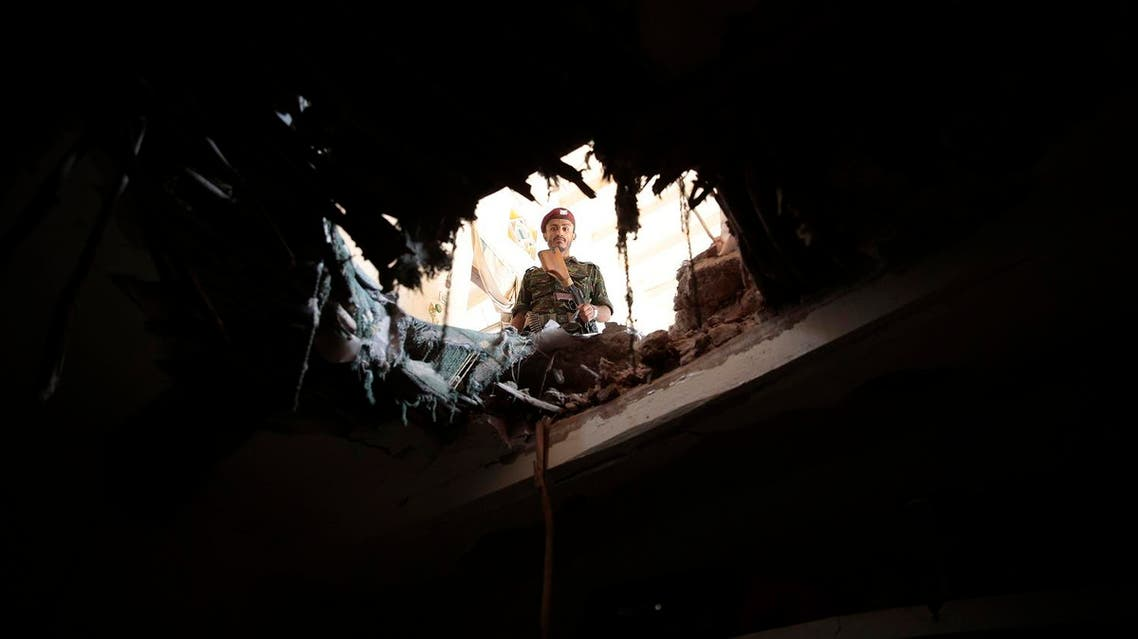 A soldier looks through a hole in a building damaged after an airstrike by Saudi-led coalition in Sanaa, Yemen. (File photo: AP)