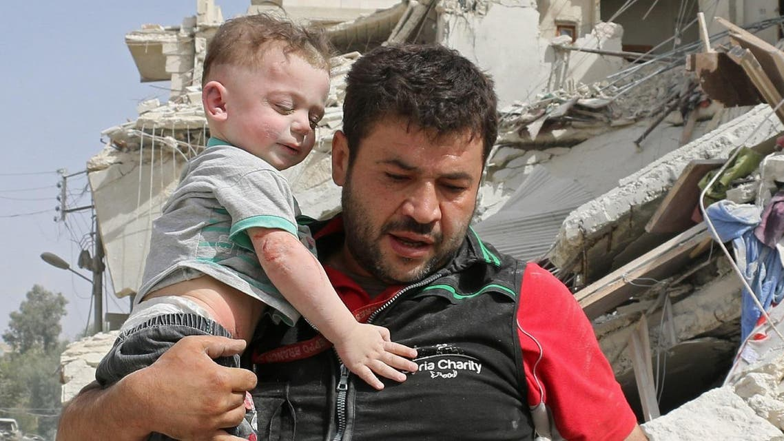 A Syrian man carries a baby after removing him from the rubble of a destroyed building following a reported air strike in the Qatarji neighbourhood of the northern city of Aleppo. (AFP)