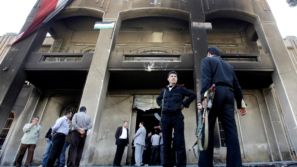 In this Monday March 21, 2011 file photo, Syrian policemen stand in front of a court building that was set on fire by Syrian anti-government protesters, in the southern city of Daraa, Syria. ap