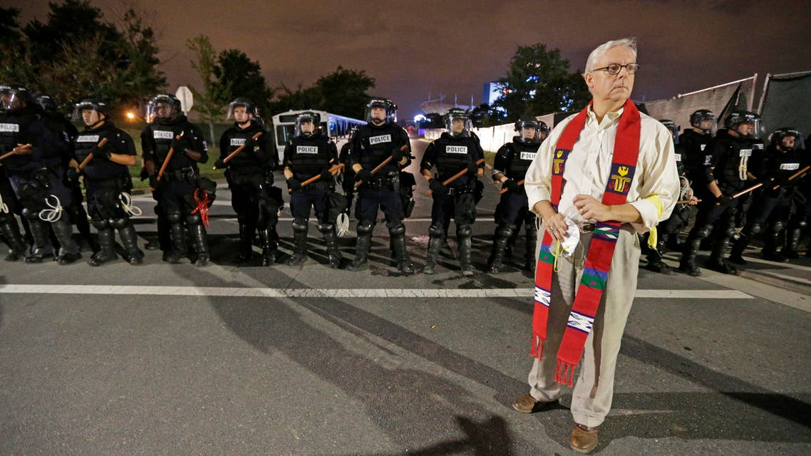 A member of the clergy stands in front of a line of police officers in Charlotte, N.C. Thursday, Sept. 22, 2016. blocking the access road to I-277 on the third night of protests following Tuesday's fatal police shooting of Keith Lamont Scott. (AP)