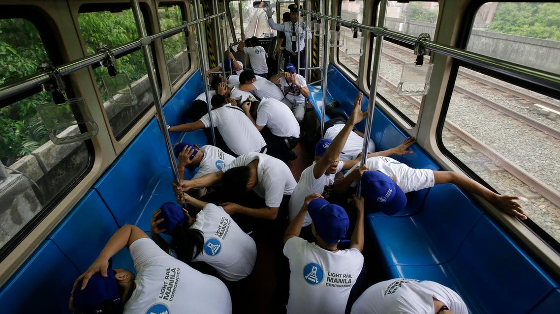 Employees duck and cover their heads as they participate in a Metro-wide earthquake drill on the Light Railway Transit, LRT, station in Manila, Philippines on Wednesday, June 22, 2016. Government agencies, schools and private companies participated in a massive drill across Manila designed to boost preparedness in the country. (AP)