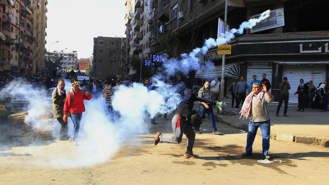 A supporter of Egypt's ousted President Mohammed Morsi throws tear gas towards Egyptian security forces in Cairo, Egypt, Friday, Dec. 27, 2013 (File Photo: AP/El Shorouk newspaper, Ahmed Abd El Latif)