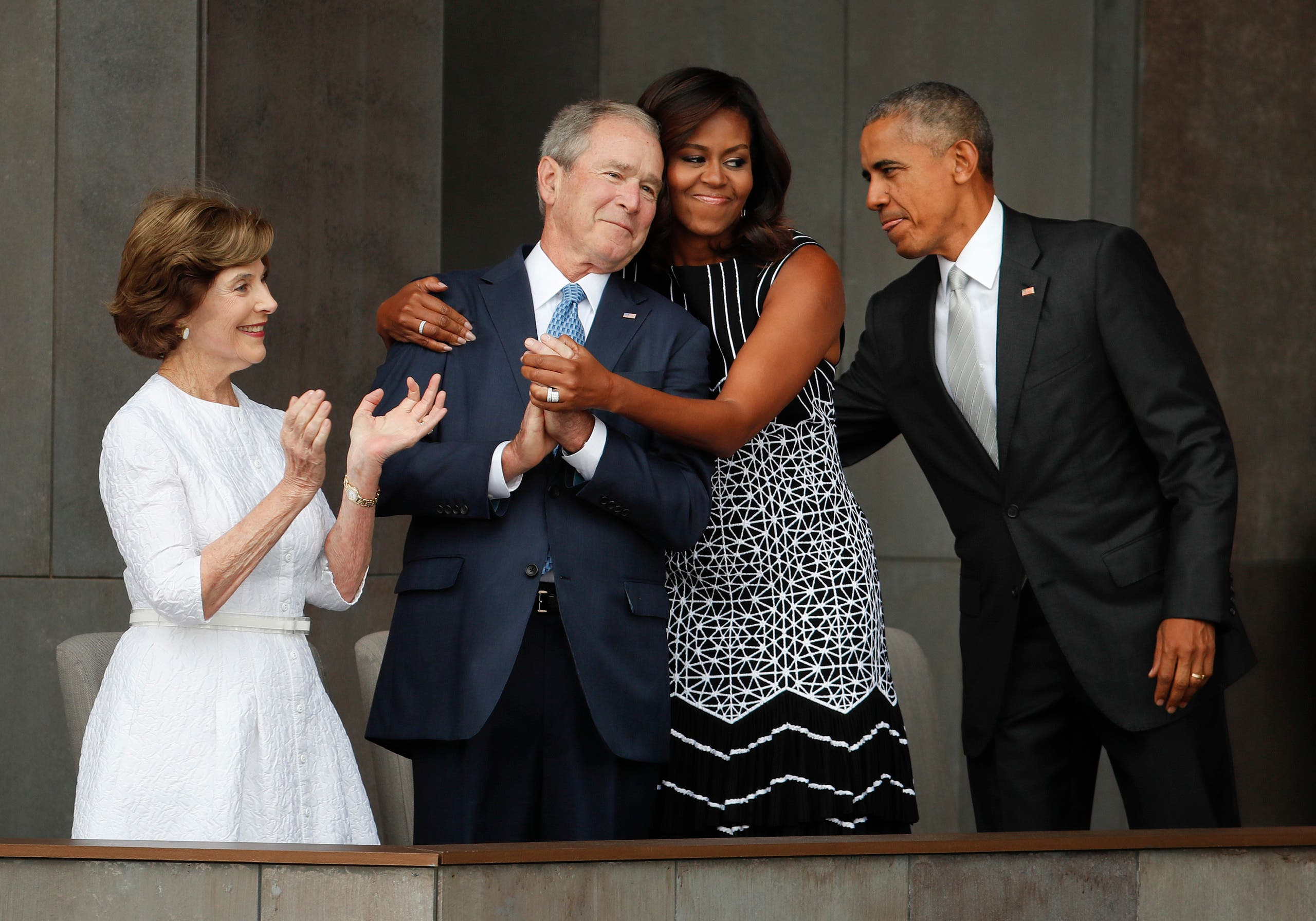 First lady Michelle Obama, center, hugs former President George W. Bush, as President Barack Obama and former first lady Laura Bush walk on stage at the dedication ceremony of the Smithsonian Museum of African American History and Culture on the National Mall in Washington, Saturday, Sept. 24, 2016. (AP)