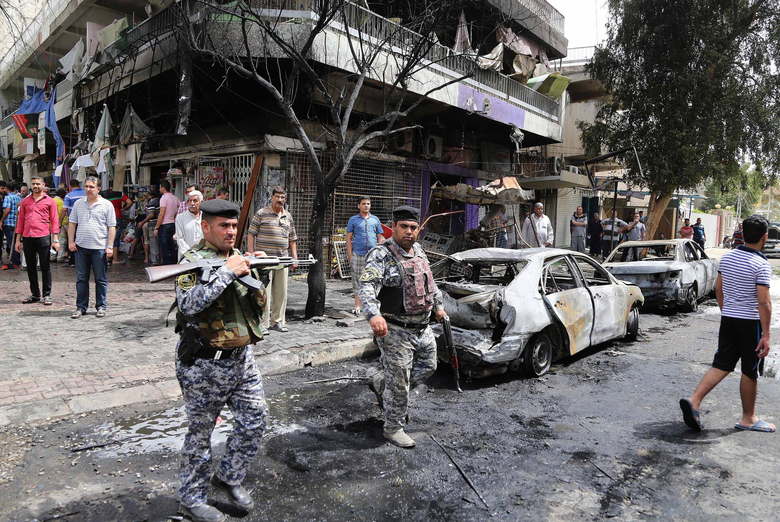 People and security forces gather at the site of a car bomb explosion at a convenience store in the Karrada neighborhood of Baghdad, Iraq. (File photo: AP)