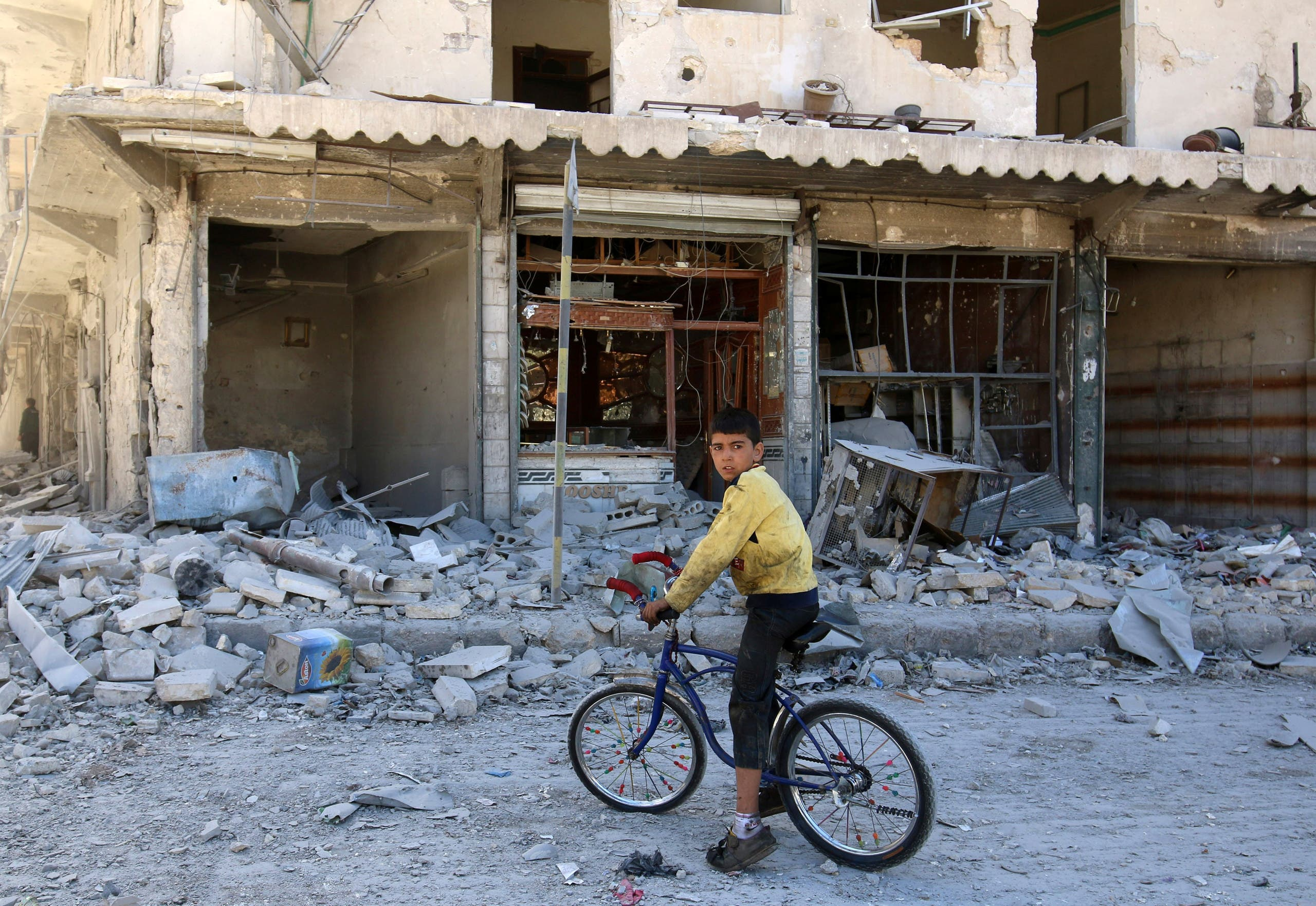 A boy sits on a bicycle in front of damaged shops after an airstrike on the rebel held al-Qaterji neighbourhood of Aleppo, Syria September 25, 2016. REUTERS/Abdalrhman Ismail
