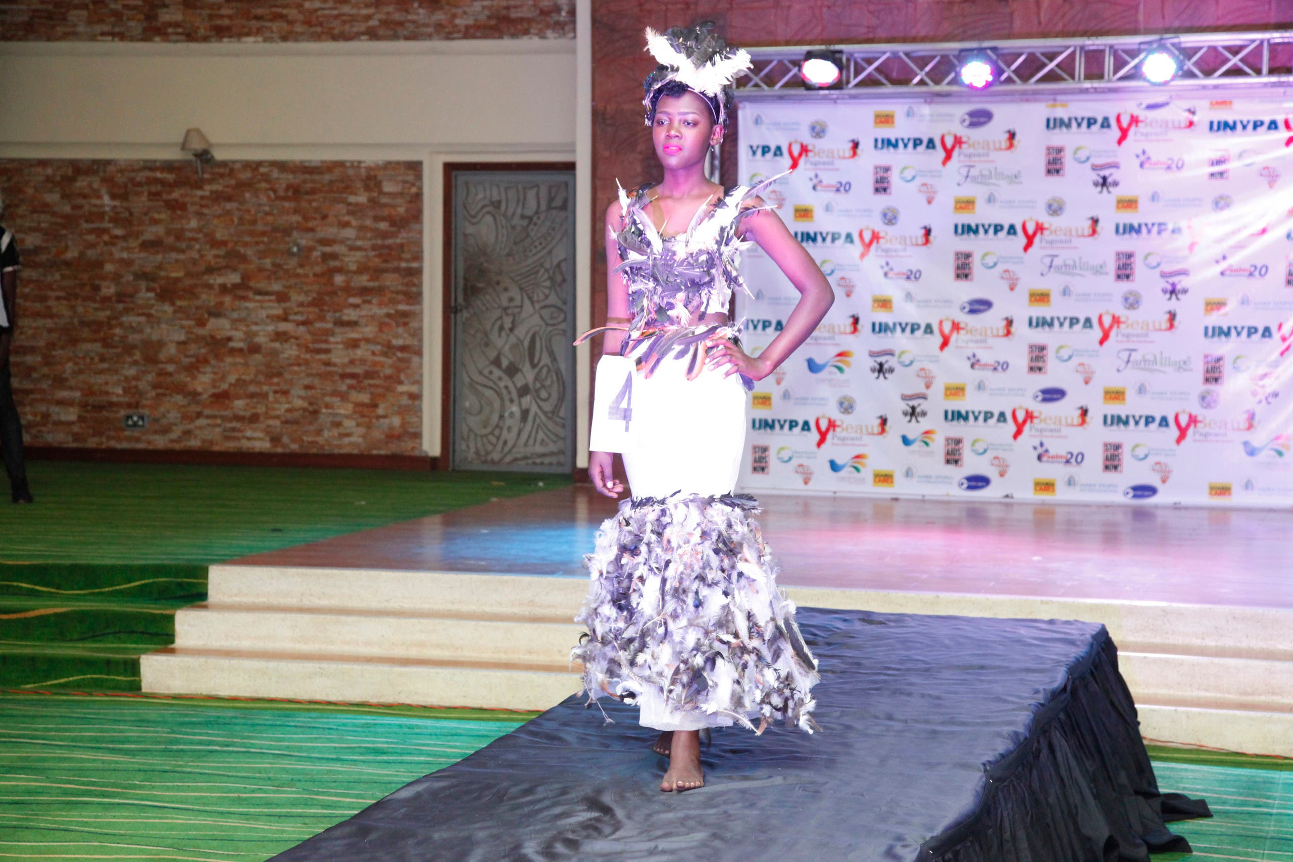 A Ugandan models a dress on the runway at the third annual Uganda Network of Young People Living with HIV beauty pageant at Golf Course Hotel Kampala, Uganda, Saturday Sept. 24, 2016.
