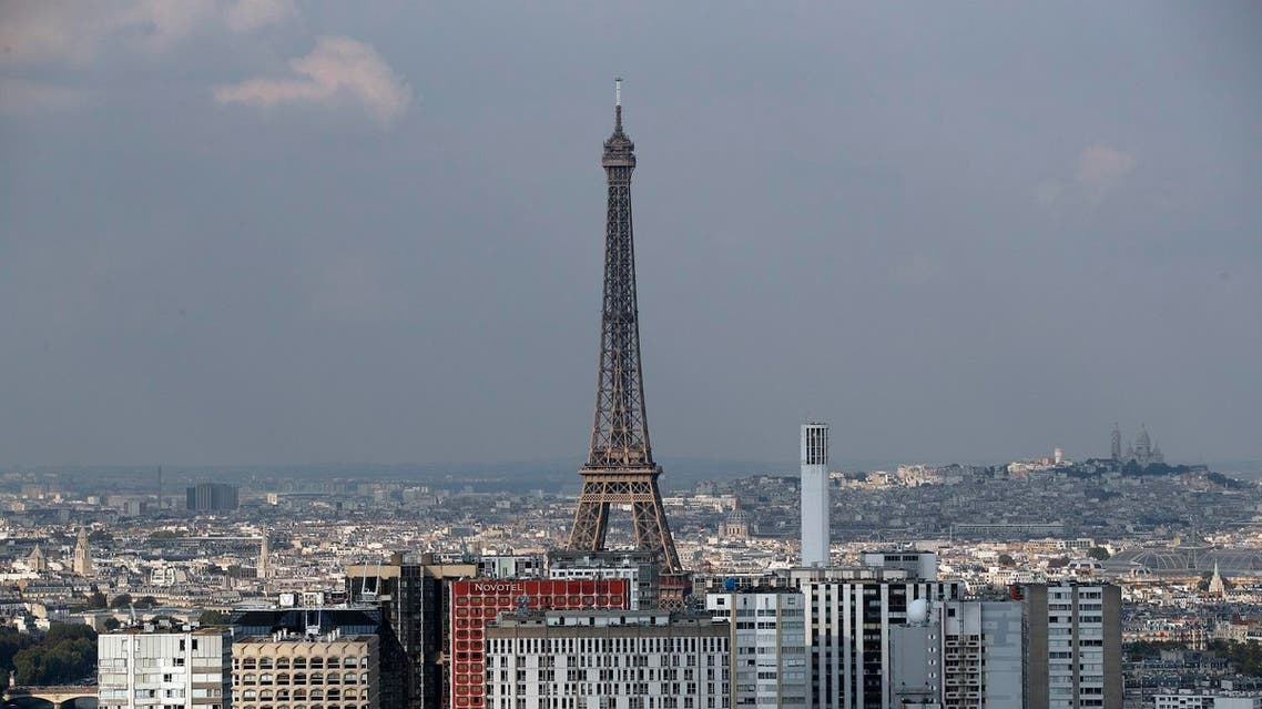 The Eiffel tower is pictured behind buildings in Paris (Photo: AP/Christophe Ena)