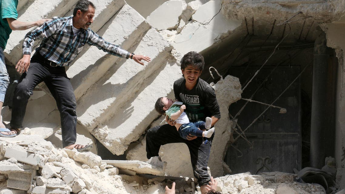Syrians evacuate a toddler from a destroyed building following a reported air strike on the rebel-held neighbourhood of al-Kalasa in the northern Syrian city of Aleppo, on April 28, 2016.  afp