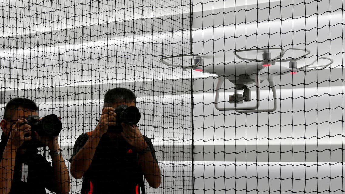 Photographers take photos of a drone flying at DJI's flagship store in Hong Kong, China September 22, 2016, two days before its opening. REUTERS
