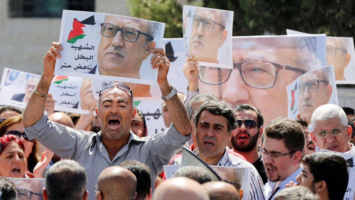 Relatives and activists hold pictures of Jordanian writer Nahed Hattar, who was shot dead, and shout slogans during a sit-in in front of the prime minister's building in Amman, Jordan, September 26, 2016. REUTERS/Muhammad Hamed