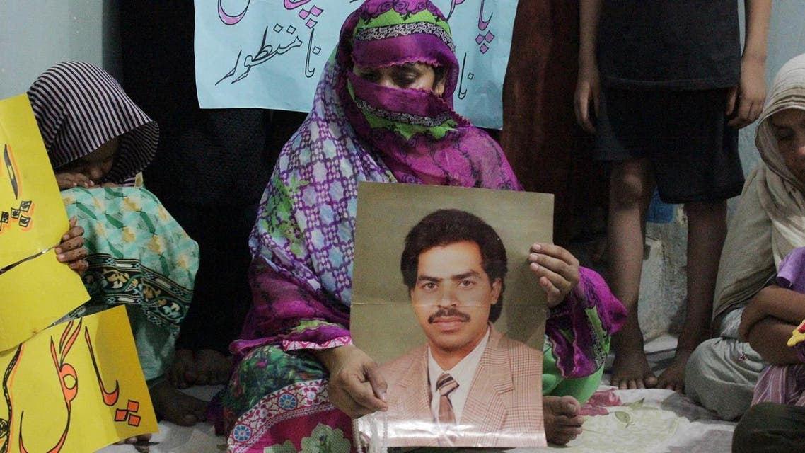 In this Sunday, Sept. 18, 2016 file photo, a Pakistani woman Safia Bano displays the picture of her husband Imdad Ali, a death row prisoner, while she sits with other family members in Burewala, in central Pakistan. An international rights group says on Tuesday, Sept. 27, 2016 Pakistan's Supreme Court has upheld the death penalty against a mentally ill man accused of murder, overturning a previous appeal and a court decision staying his execution. (AP Photo/Asghar Ali, File)