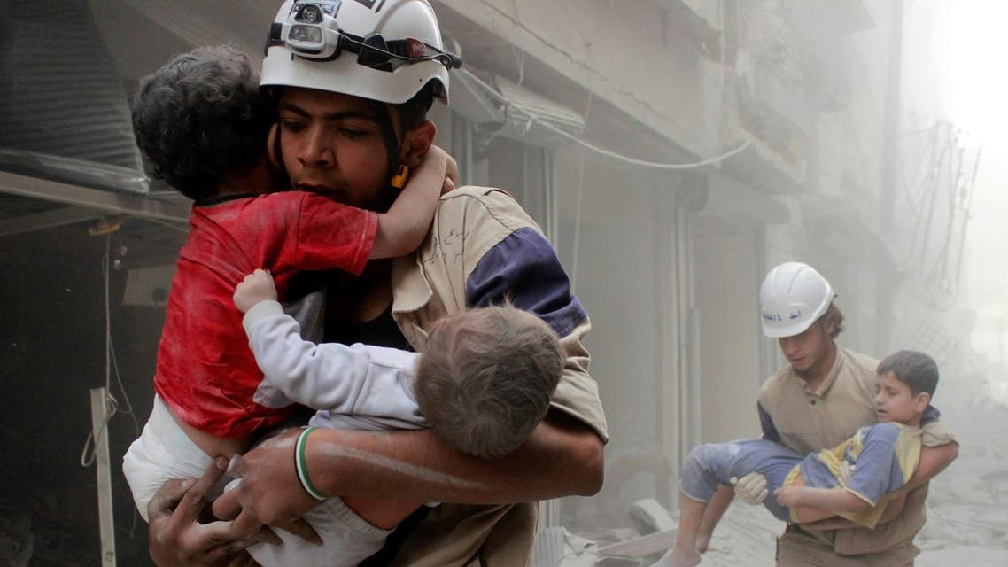 Members of the Civil Defence rescue children after what activists said was an air strike by forces loyal to Syria's President Bashar al-Assad in al-Shaar neighbourhood of Aleppo, Syria June 2, 2014. REUTERS/Sultan Kitaz/File Photo TPX IMAGES OF THE DAY