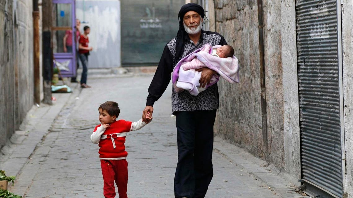 Abu Ahmad carries his baby, Jalal, while walking with his daughter Amal in the Al-Shaar neighbourhood of Aleppo. (File photo: Reuters)