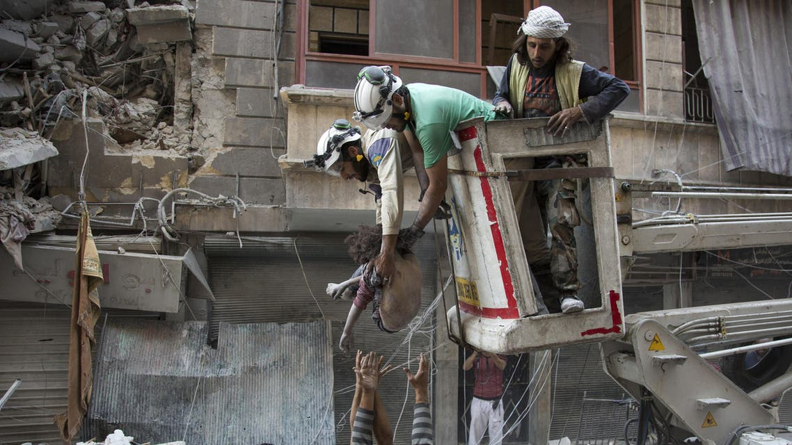 Syrian rescuers hand the body of a girl down to civilians on the ground after she was pulled from rubble of a budling following government forces air strikes in the rebel held neighbourhood of Al-Shaar in Aleppo on September 27, 2016. Syria's army took control of a rebel-held district in central Aleppo, after days of heavy air strikes that have killed dozens and sparked allegations of war crimes. (AFP)