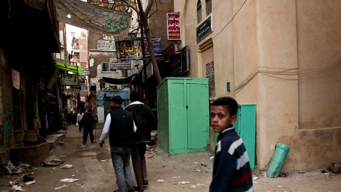 In this Monday, Nov. 26, 2012 file photo, residents pass a kiosk, center, that is used as a clinic where girls are circumcised by a barber, in the Imbaba area of Giza, Egypt.