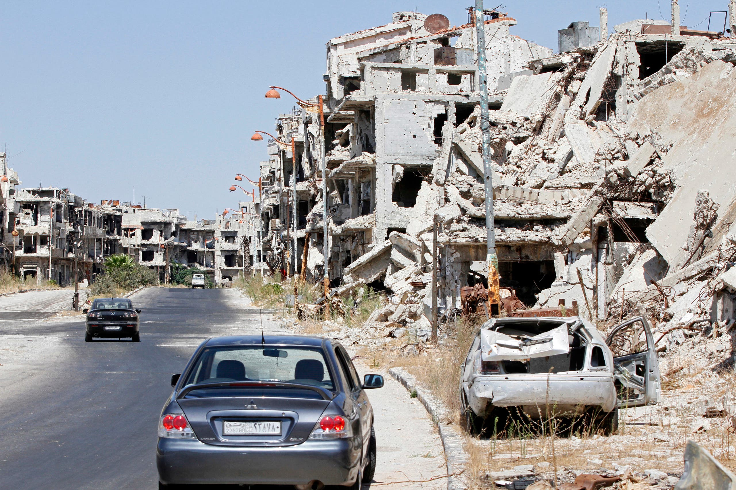 Damaged buildings and rubble line a street in Homs, Syria, Sept. 19, 2016. (ap)