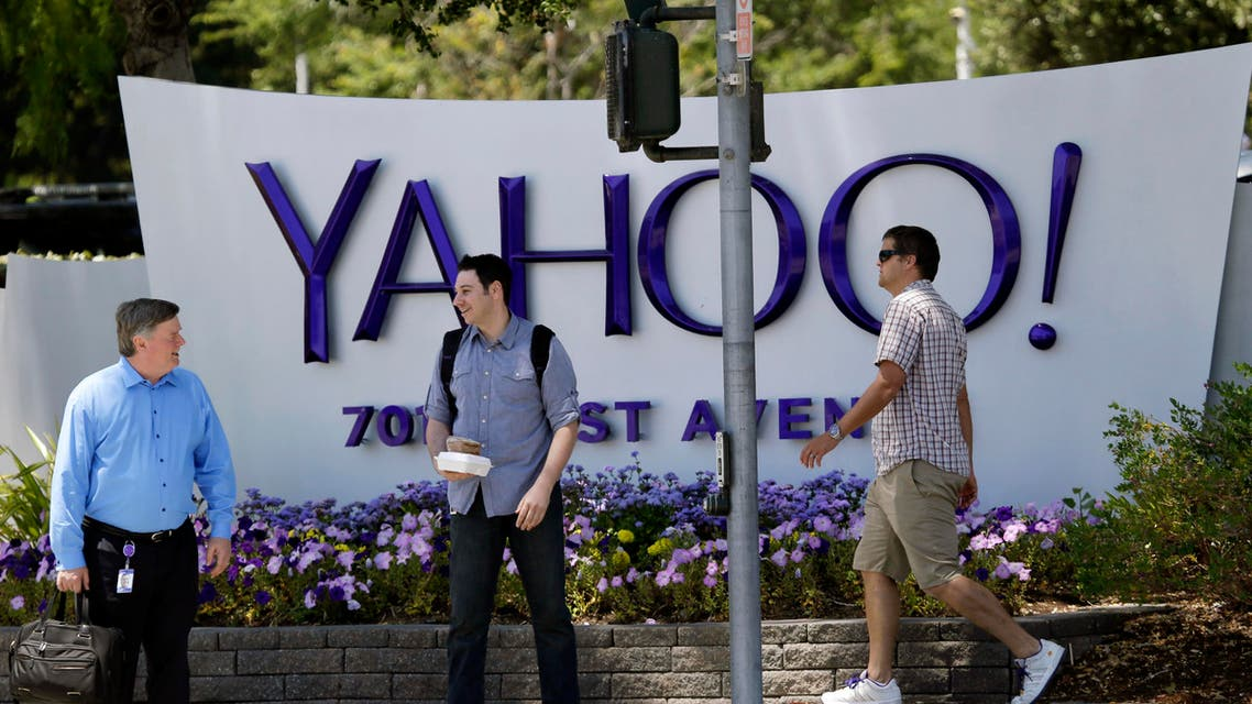 In this June 5, 2014 photo, people walk in front of a Yahoo sign at the company's headquarters in Sunnyvale, Calif. Yahoo Inc. reports quarterly financial results on Tuesday, Oct. 21, 2014. (AP