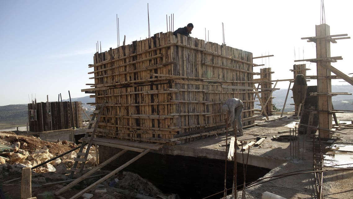 This file photo taken on February 22, 2012 shows Palestinian workers constructing new houses in the Jewish settlement of Shilo in the West Bank. Israel has approved on October 1, 2016. (File photo: AFP)