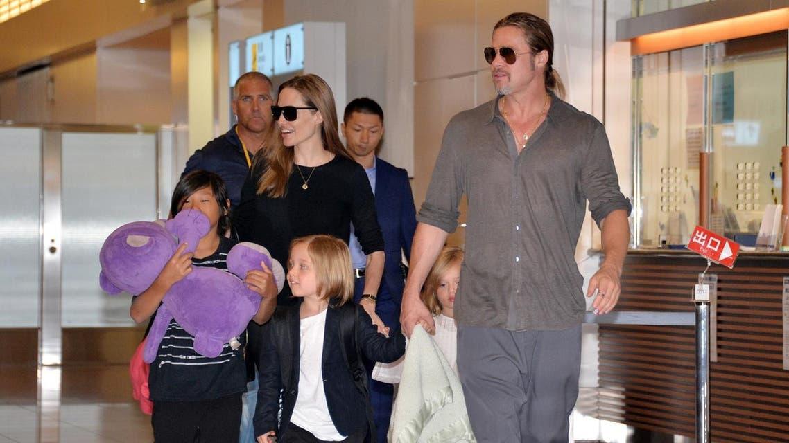 "US film stars Brad Pitt (R) and Angelina Jolie (C), accompanied by their children, arrive at Haneda International Airport in Tokyo on July 28, 2013. Pitt is now here for the promotion of his latest movie ""World War Z"". AFP PHOTO / Yoshikazu TSUNO YOSHIKAZU TSUNO / AFP"