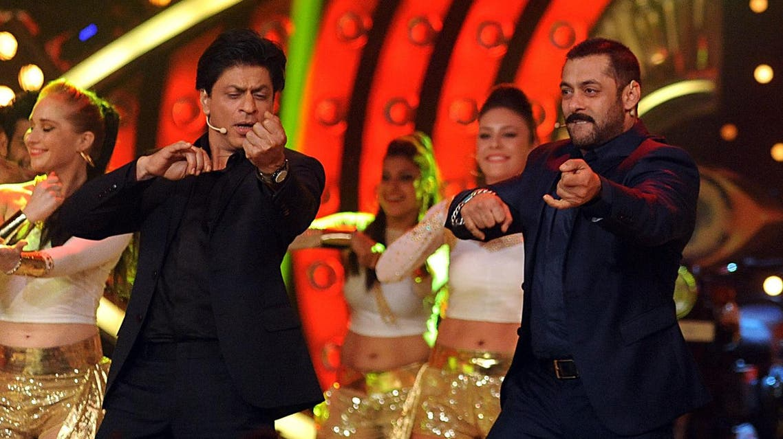 ndian Bollywood actors Shah Rukh Khan (L) and Salman Khan (R) perform with dancers during a promotional event for the Hindi film 'Dilwale' on the set of Colors 'Bigg Boss Nau 'Double Trouble' TV Reality Show in Lonavala some 100kms from Mumbai on December 19, 2015. AFP PHOTO/Sujit Jaiswal. SUJIT JAISWAL / AFP