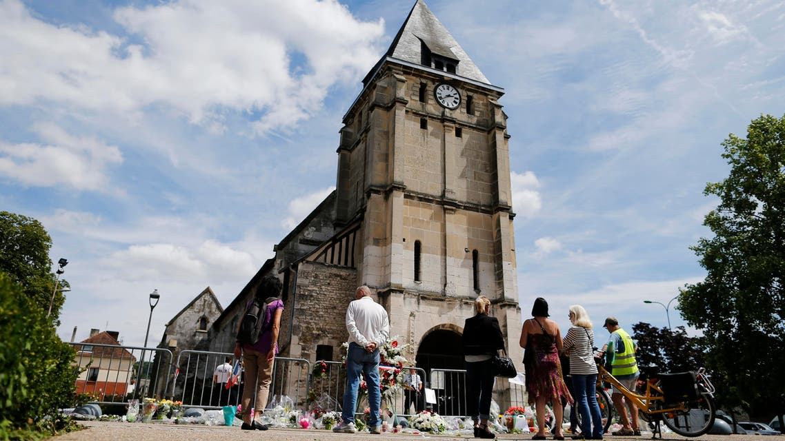 people gathering on July 28, 2016 near floral in front of the church of Saint-Etienne-du-Rouvray, northern France, where French priest Jacques Hamel was killed on July 26 in the church during a hostage-taking claimed by Islamic State group. (AFP)