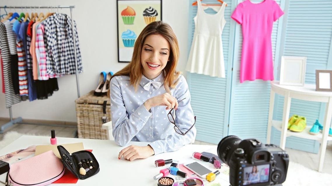 Young female blogger with makeup cosmetics recording video at home shutterstock